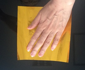 金色の折り紙に左手を乗せた