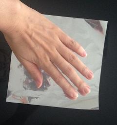銀色の折り紙に左手を乗せた