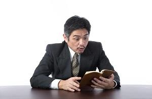 手帳を見て驚くスーツ男性
