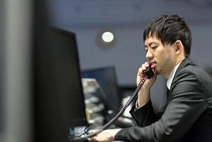 職場で電話しているスーツ男性
