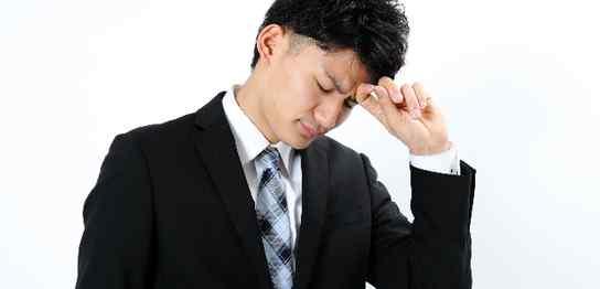 頭が痛いスーツ男性