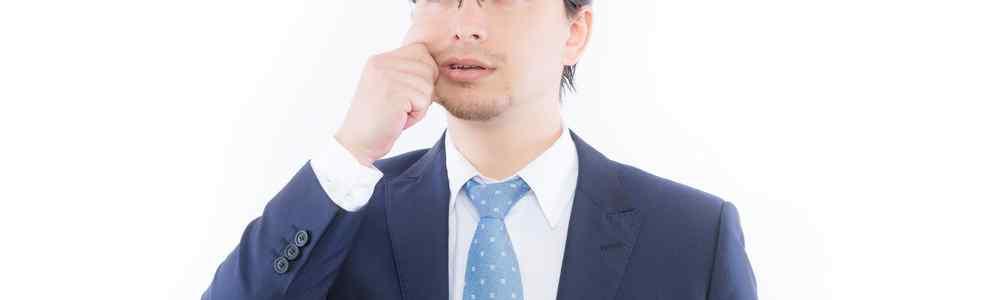 右頬をつねるスーツ男性