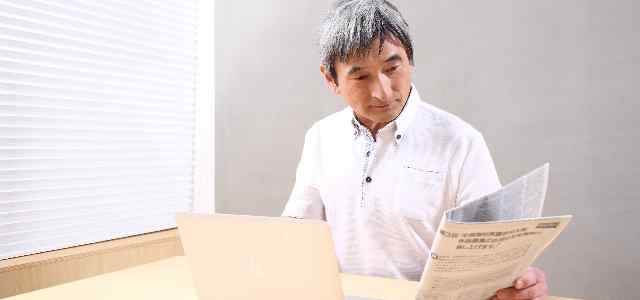 ノートパソコンと新聞を見ている白髪の男性
