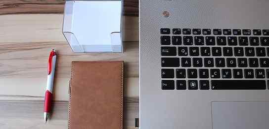 ノートパソコンの左横にメモと手帳とペン