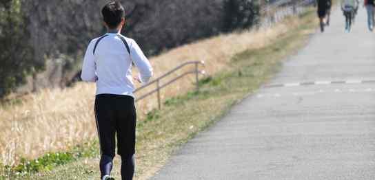 土手をジョギングする男性