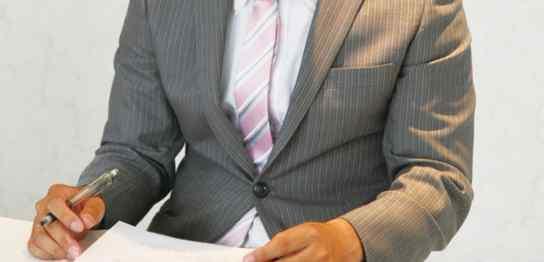 ノートに書き込むスーツ男性