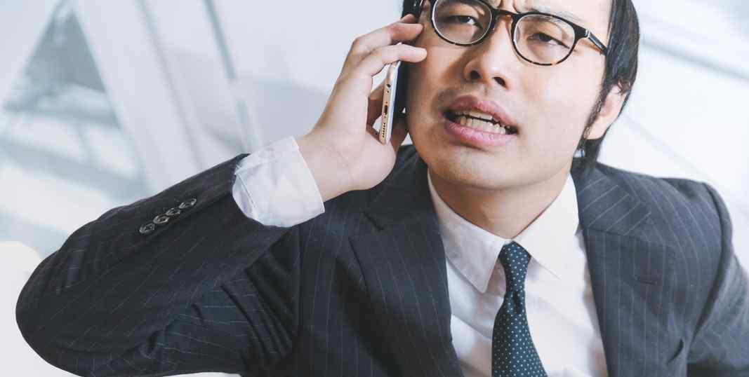 スマホで通話中のスーツ男性