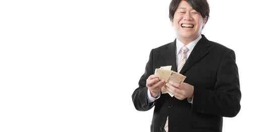 お金を持って笑顔のスーツ男性