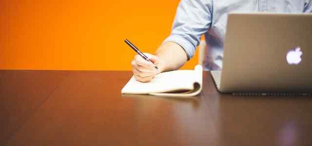 Macbookを操作しながらノートにメモしている男性