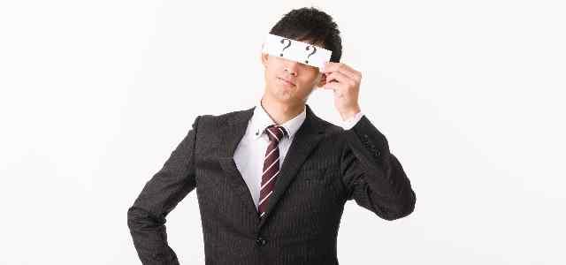 「??」で目隠ししているスーツ男性