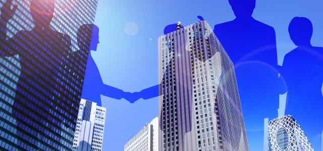 高層ビルを背景にビジネスマン達のシルエット