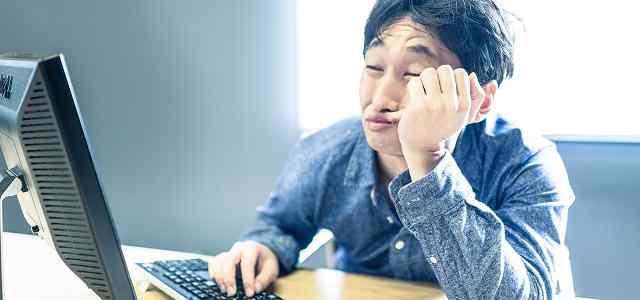 パソコンの前でひじをついている男性