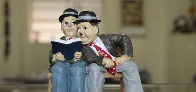 隣の人の本をのぞき込む人の人形