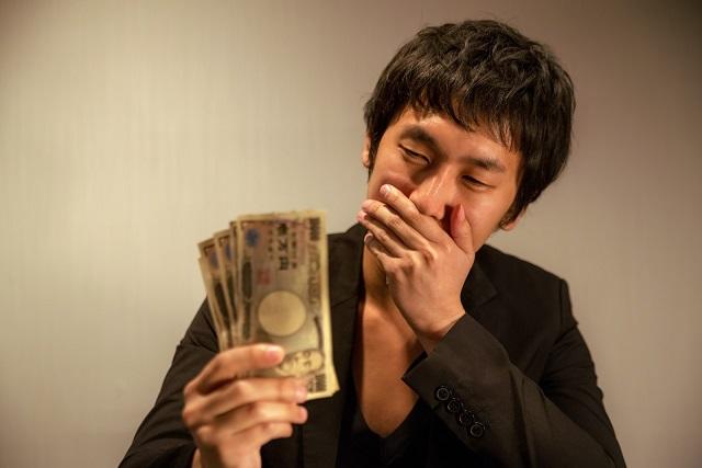 1万円札を見てにやける男性