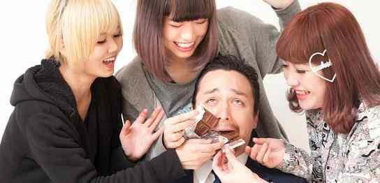 3人の女性にチョコレートを食べさせられるスーツの男性
