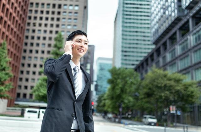 ビジネス街で携帯電話中の若手スーツ男性
