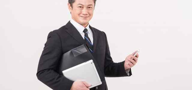 スマホとノートPCを持った中年スーツ男性