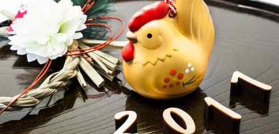 黒いお盆の上に金の鶏と「2011」の文字