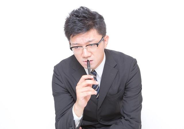 ペンを口元にあてて考えるスーツ男性