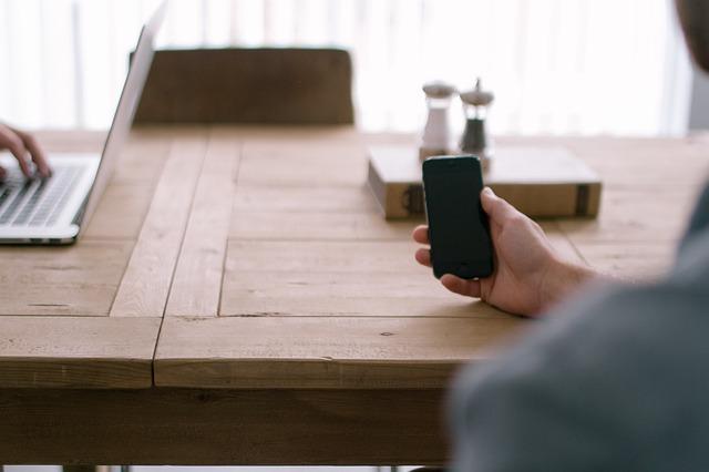 お洒落な木のテーブルでMacbookとiPhoneを操作している二人