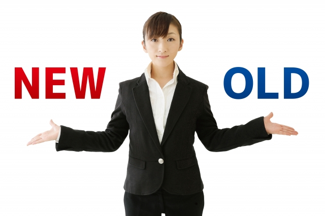「NEW」「OLD」の文字を両手に持ったスーツ女性
