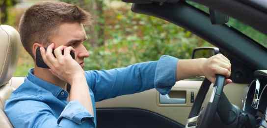 オープンカーを運転しながら電話している男性