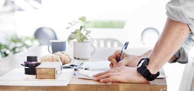 テーブルでメモを書く男性