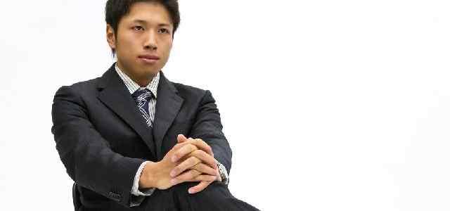 足を組んで座っているスーツ男性