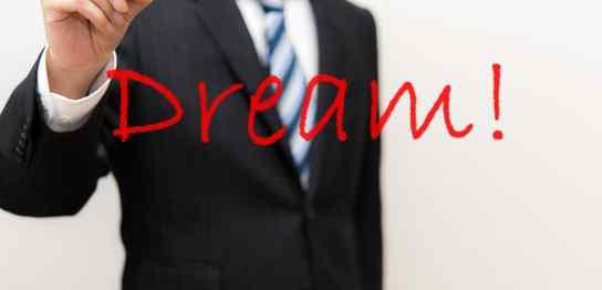 透明の壁に赤字で「Dream」と書くスーツ男性