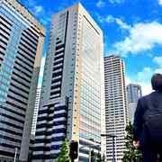 高層ビルを見上げるリュックをしょった男性