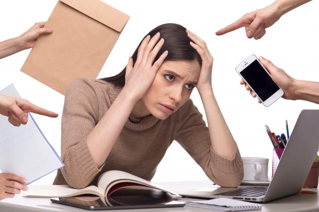 沢山仕事が降ってきて多忙で頭を抱える女性