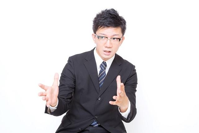 両手を使って説明するスーツ男性