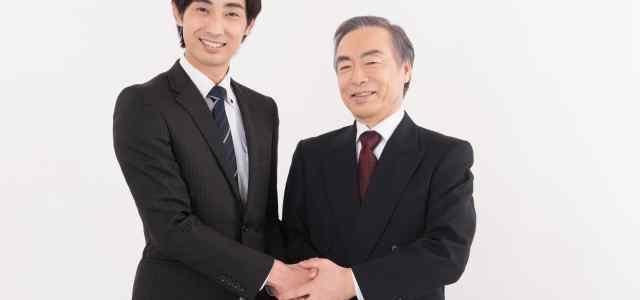 若手と年配のスーツ男性が握手