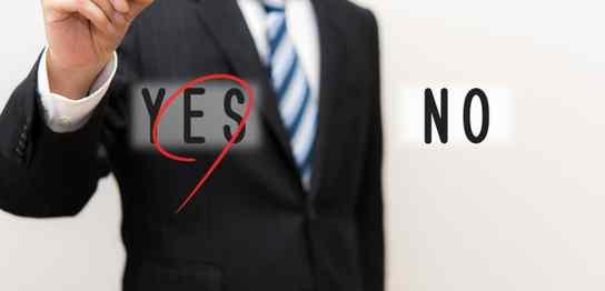 透明の壁に書いてある「YES」に丸をつける男性