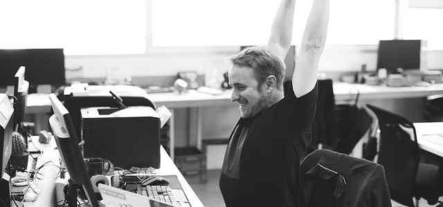 オフィスで座ったまま伸びをしている男性