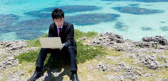 海辺でノートPCで仕事する男性