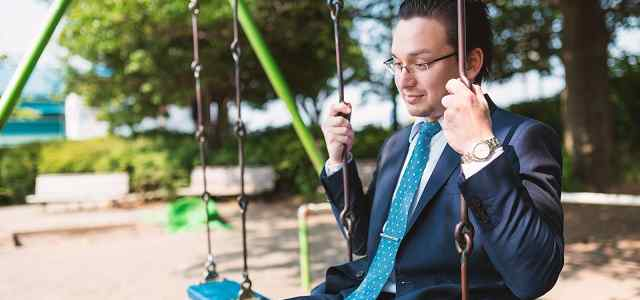 公園のブランコに乗るサラリーマン