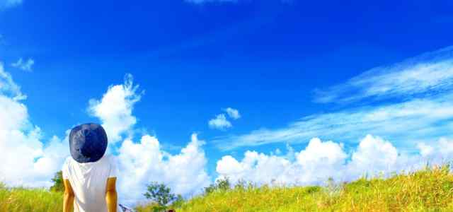 道に座って青空を見上げている男性