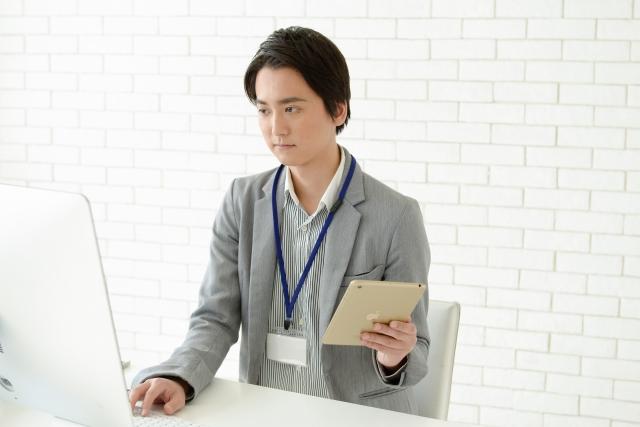 パソコンとタブレットで仕事する男性