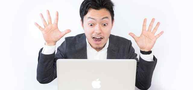 Macbookの前でびっくりする男性