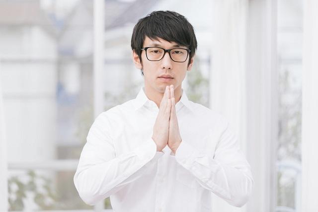 両手を合わせている白いワイシャツのメガネ男子