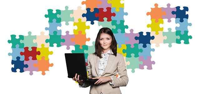 ジグソーパズルの前でノートPCを持って立っている女性