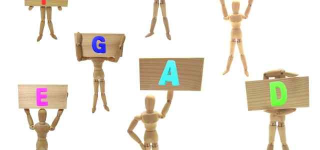 アルファベットの文字を持っている木の人形達