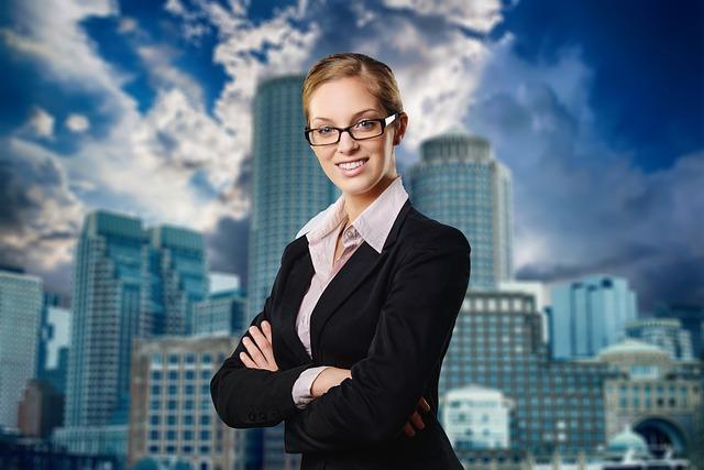 高層ビルを背景に腕を組んだスーツの眼鏡女性