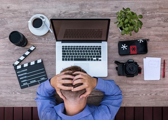 ノートパソコンの前で頭を抱える青いワイシャツの男性