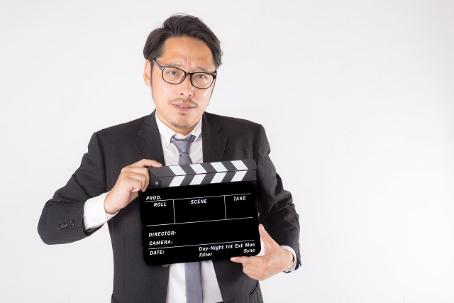 映画監督のようにカチンコを持ったスーツ男性