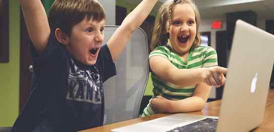 Macbookの前で喜んでいる子供2人