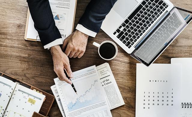 ノートパソコンとスーツ男性の両腕とコーヒーと書類を上から写した写真