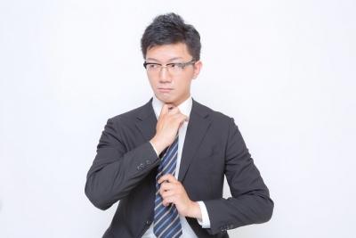 ネクタイをギュッと絞めるスーツ男性
