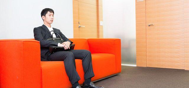 待合室で緊張するスーツ姿の男